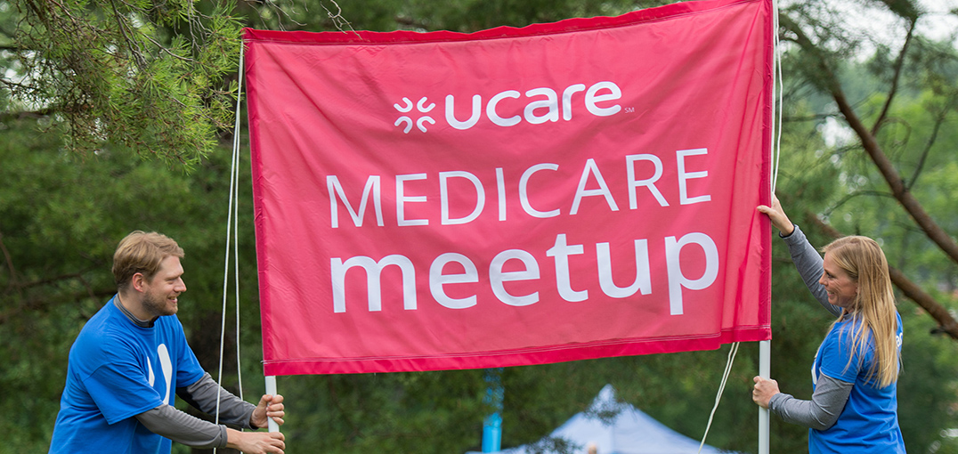 UCare employees holding a Medicare Meetup banner