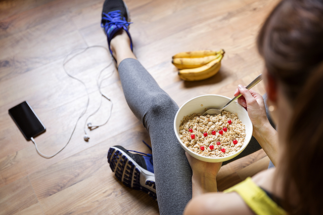 woman in exercise clothes eating cereal